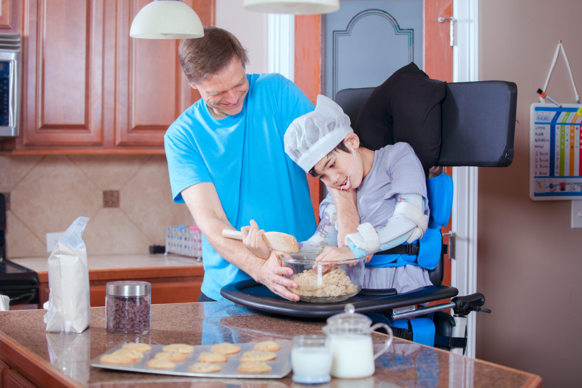 Father helping disabled son bake cookies in kitchen
