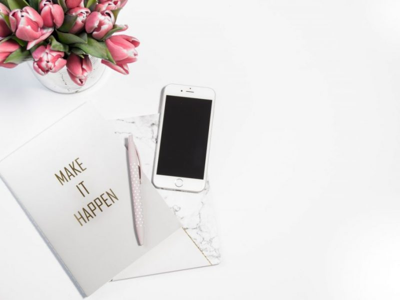 notebook and phone on table to set goals in life